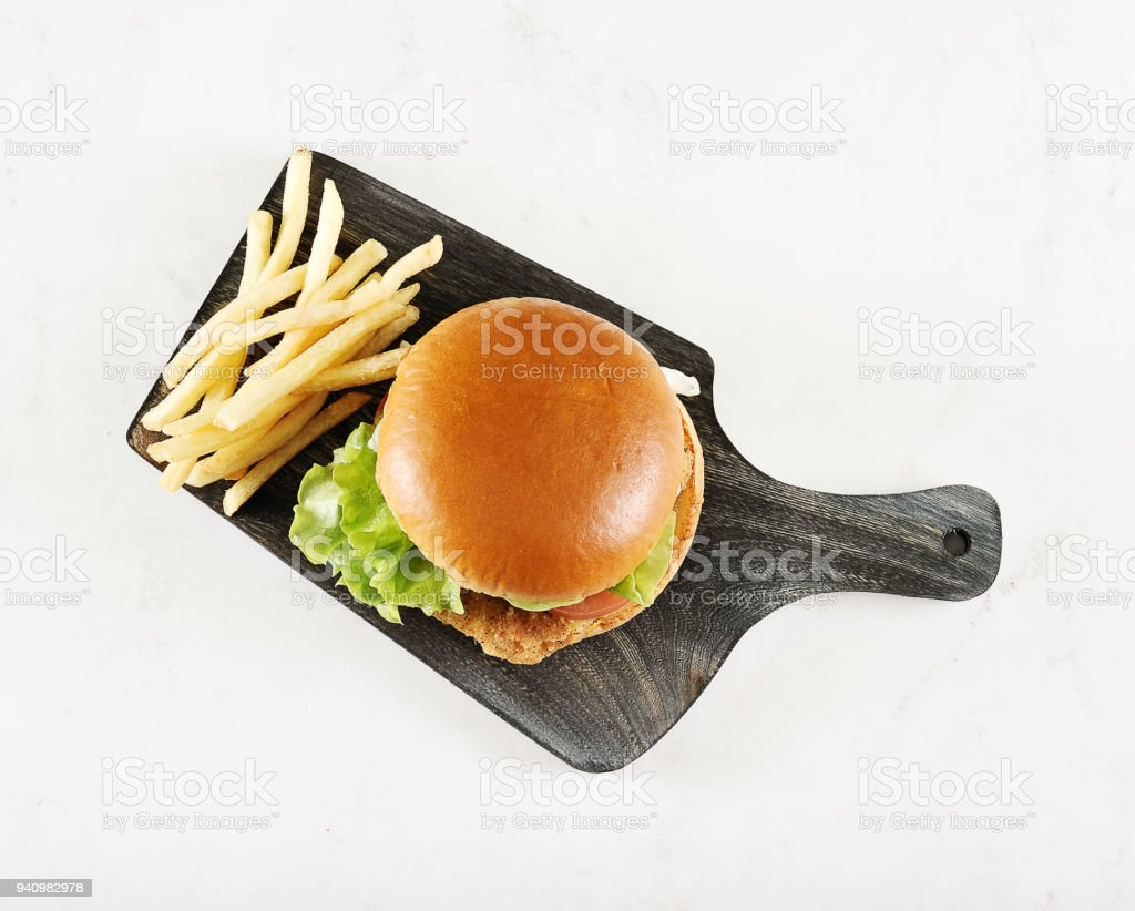 round hamburger with chicken cutlet and French fries stock photo