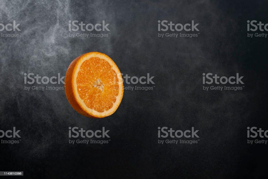 Round juicy fresh orange orange slice on black gradient background
