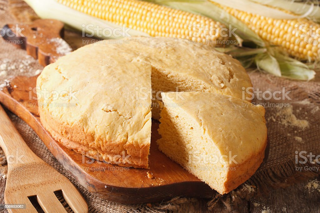 Round loaf of corn bread close-up on wooden board. Horizontal stock photo
