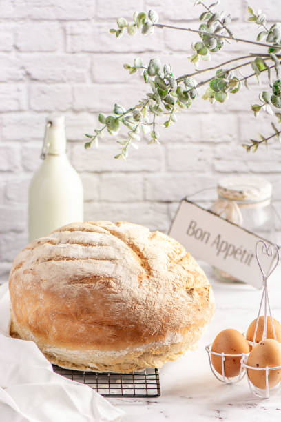 Round loaf of  white bread. Round loaf of freshly backed homemade white bread. Hight key. round loaf stock pictures, royalty-free photos & images