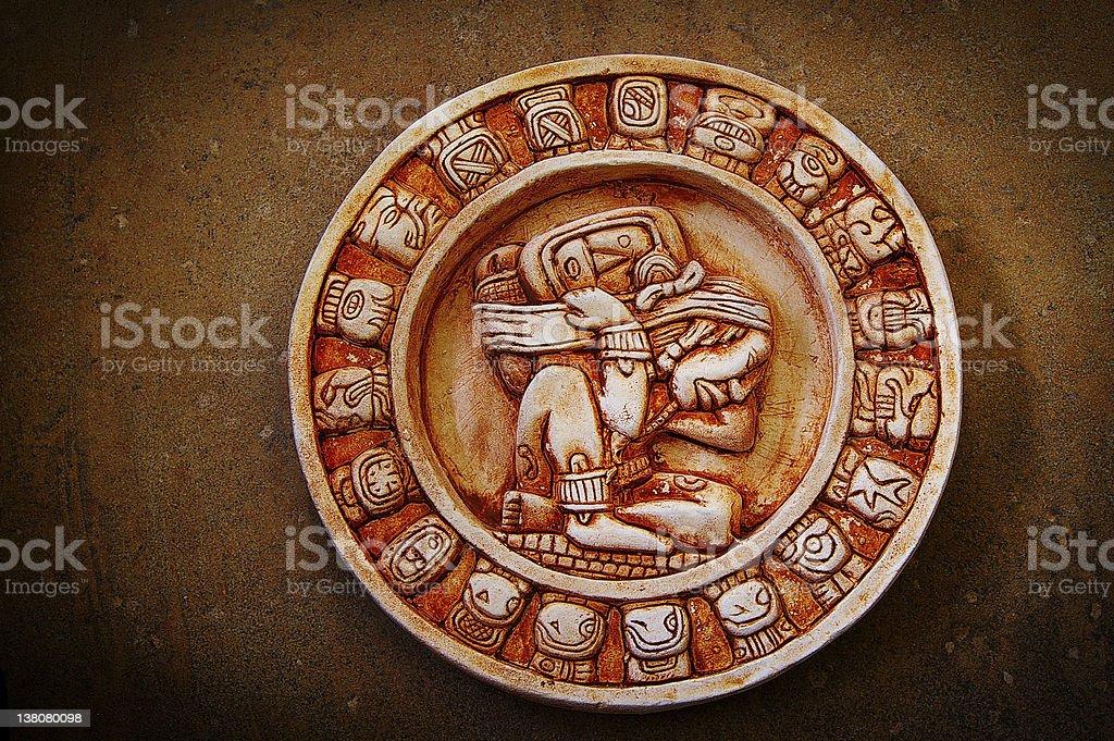 Round Mayan calendar stone on brown backdrop stock photo