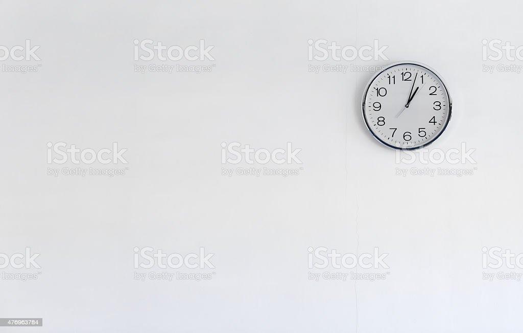 Round metal clock on white wall stock photo