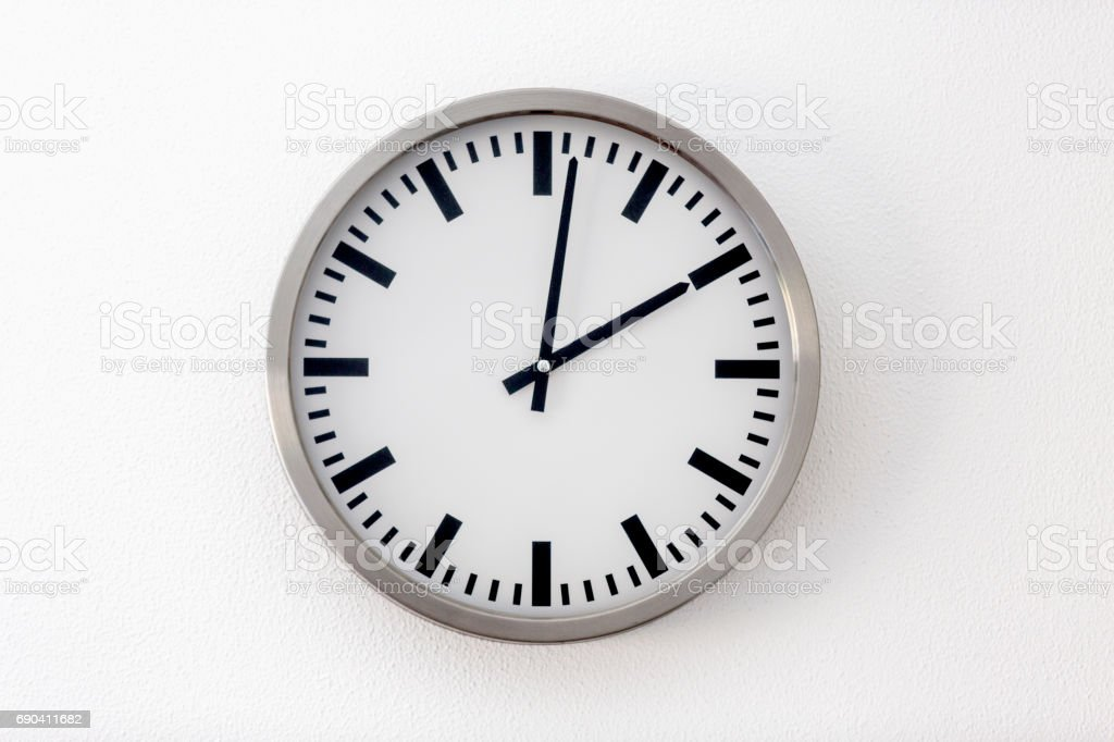 Round metal clock on white wall stock photo