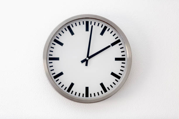 Round metal clock on white wall Round metal clock on white wall clock hand stock pictures, royalty-free photos & images