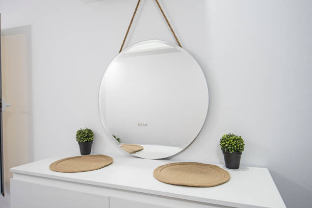 Round mirror on dresser unit in luxury home stock photo