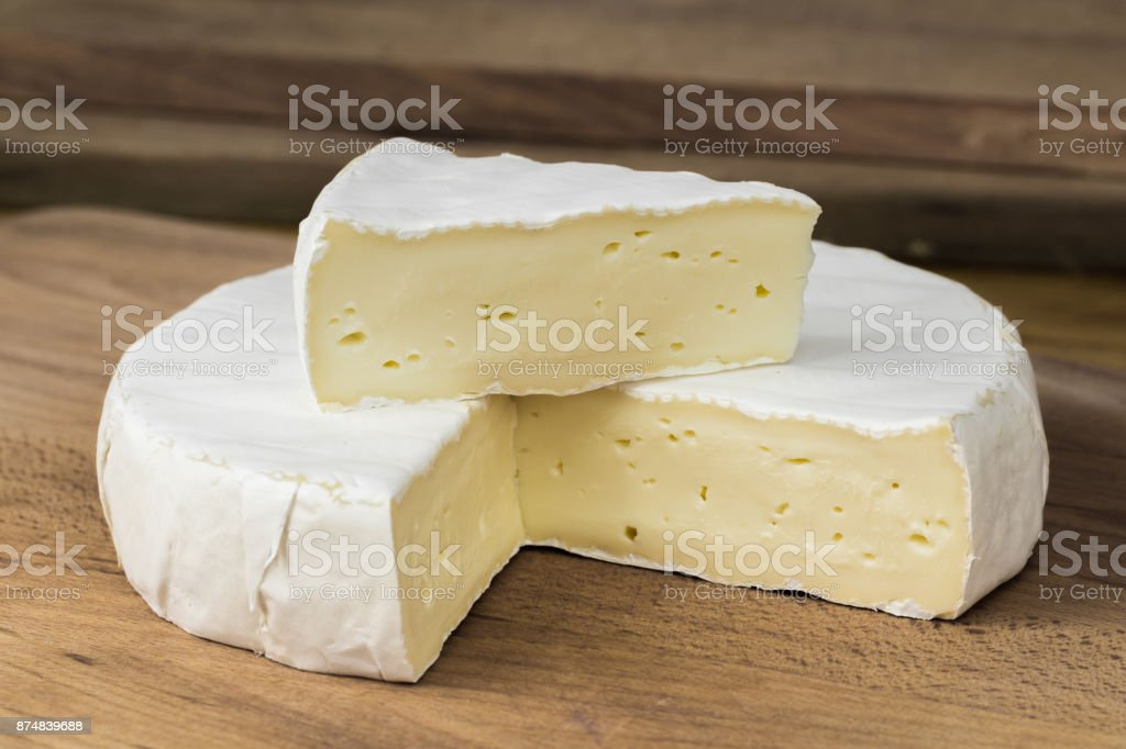 Round of Camembert cheese brie with triangle cut out placed on top . stock photo