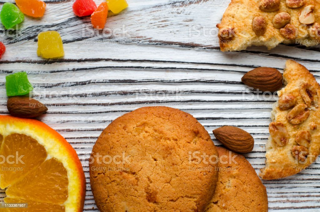 Round orange biscuits with colorful candied fruits and a slice of juicy orange lying on a wooden table stock photo