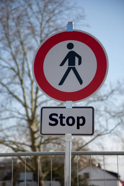 A round road sign in white and red with a black man in the center and an additional sign: no pedestrians allowed to proceed, stop