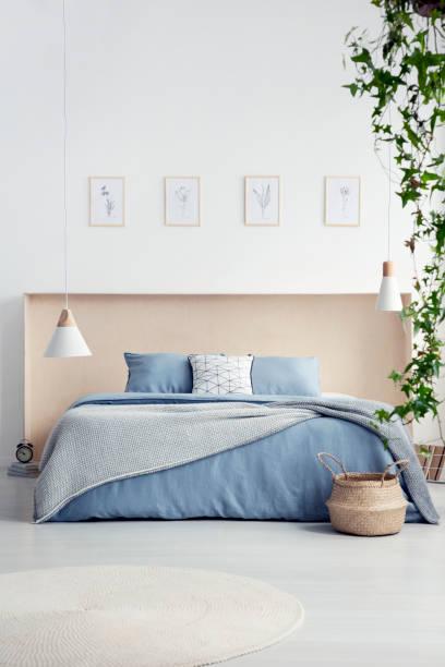 runder teppich und lampe innen weiße schlafzimmer mit plakaten über blauen bett mit decke. echtes foto - do it yourself hochbett stock-fotos und bilder