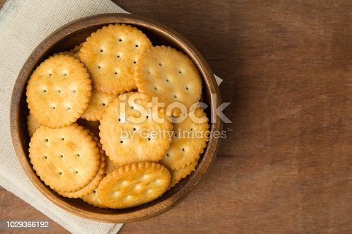 istock Round salted cracker cookies in wooden bowl putting on linen and wooden background 1029366192