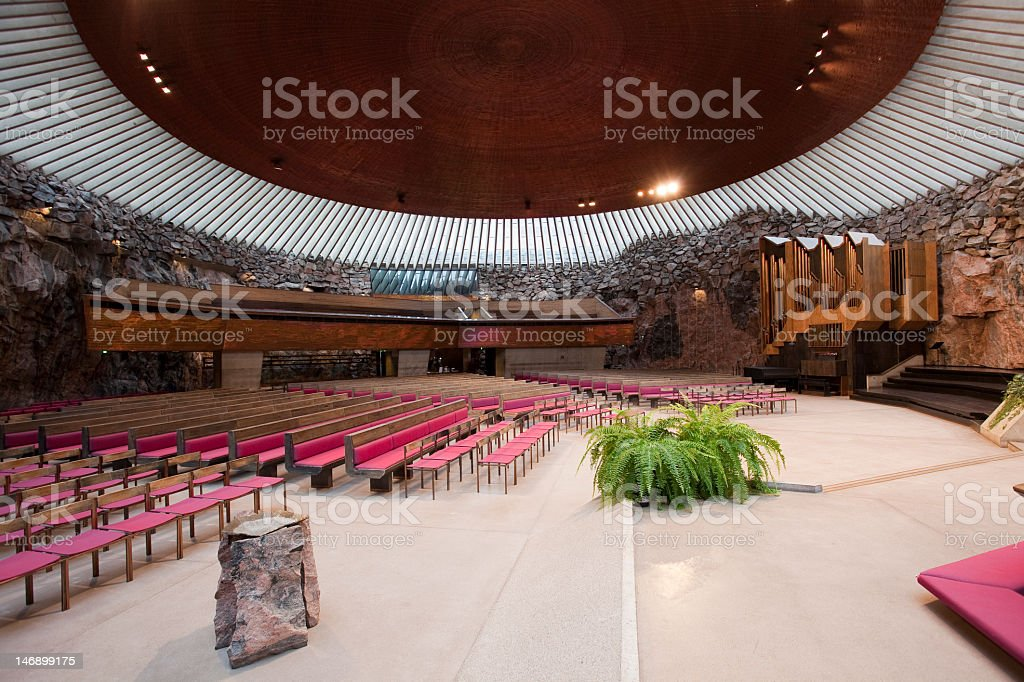 Round sanctuary of a church with rock walls and red pews stock photo