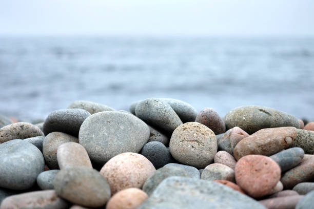 Round sea stones in front of water stock photo