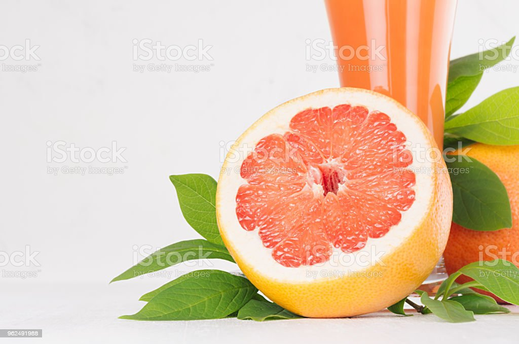 Round slice grapefruits closeup with pink juice and green leaves on white wood table, copy space, macro. - Royalty-free Circle Stock Photo