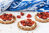 Round slices of wholemeal bread with grilled tomatoes and herbs on cream cheese.