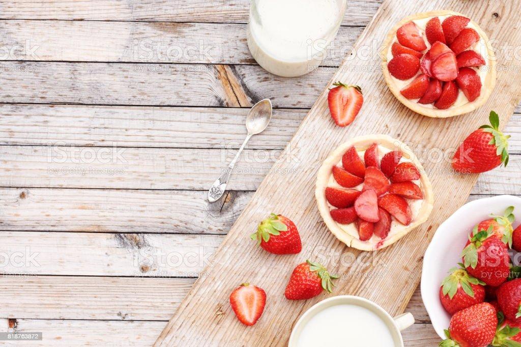 Runde Erdbeertörtchen mit Mascarpone, Schale mit frischen Erdbeeren und Tasse Milch auf rustikalen Tisch mit Textfreiraum. – Foto