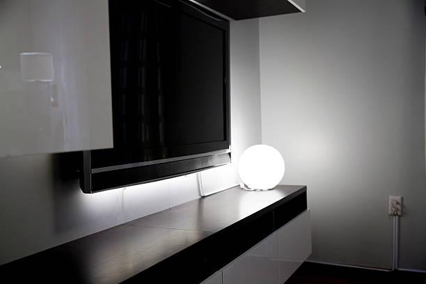 runder tisch-lampe im dunklen wohnzimmer - dekoration rund um den fernseher stock-fotos und bilder
