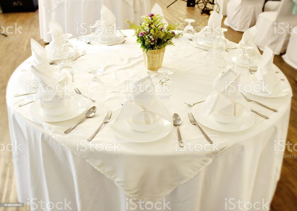 Round table with white cloth, food set and flower bouquet in center...