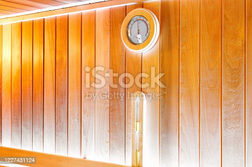 Round thermometer and hourglass on the wall of traditional wooden sauna