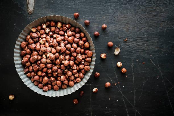 Round Tin of Shelled Hazelnuts on Black stock photo
