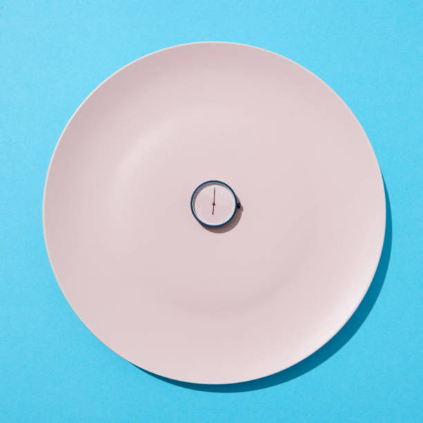 Round watch six o'clock on white plate on a blue background. Time to eat and diet concept. Place for text. Top view. stock photo