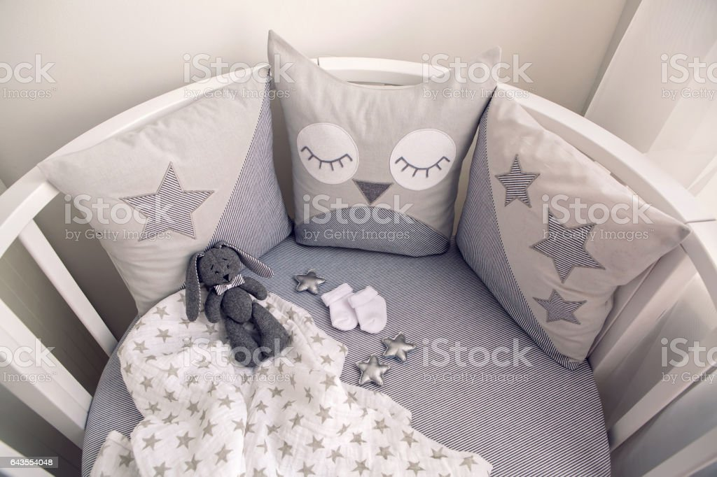 round white baby bed with gray pillows stock photo