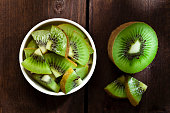Healthy eating concept: Top view of a round white  bowl filled with kiwi slices shot on rustic wood table. Some kiwi slices are out of the bowl directly on the table. DSRL studio photo taken with Canon EOS 5D Mk II and Canon EF 100mm f/2.8L Macro IS USM