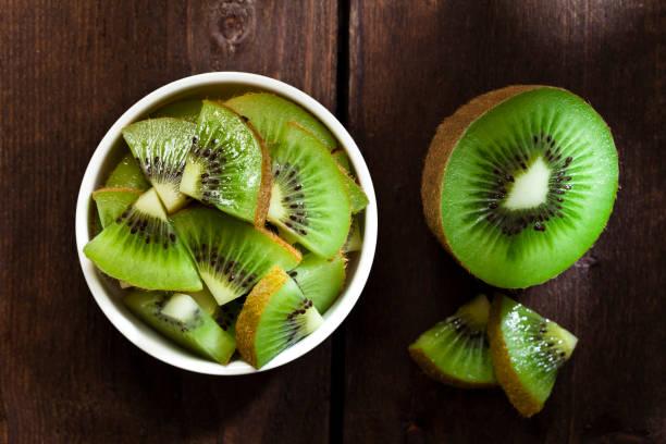 round white bowl filled with kiwi slices - kiwi imagens e fotografias de stock