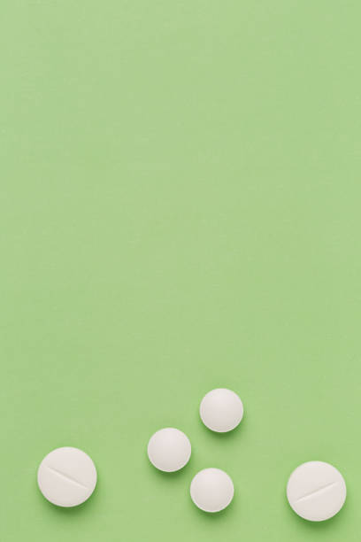 Round white pills on colorful background stock photo