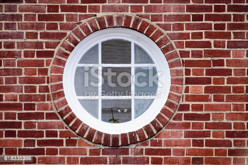 Round window in a brick wall with white frame