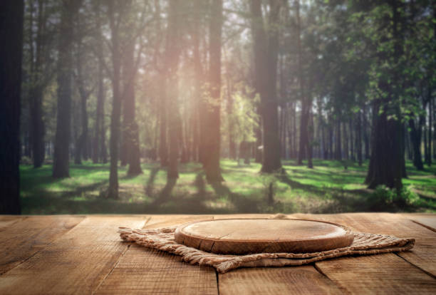 Round wood board on a wooden table on a forest background stock photo