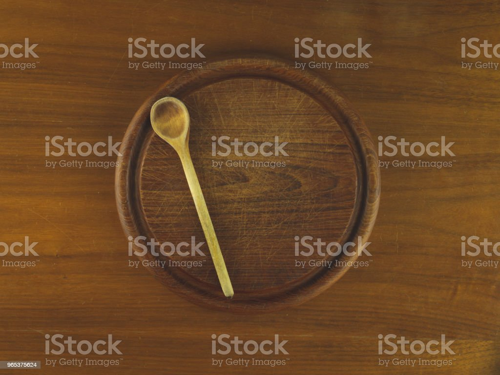 Round wooden cutting board with a wooden spoon royalty-free stock photo