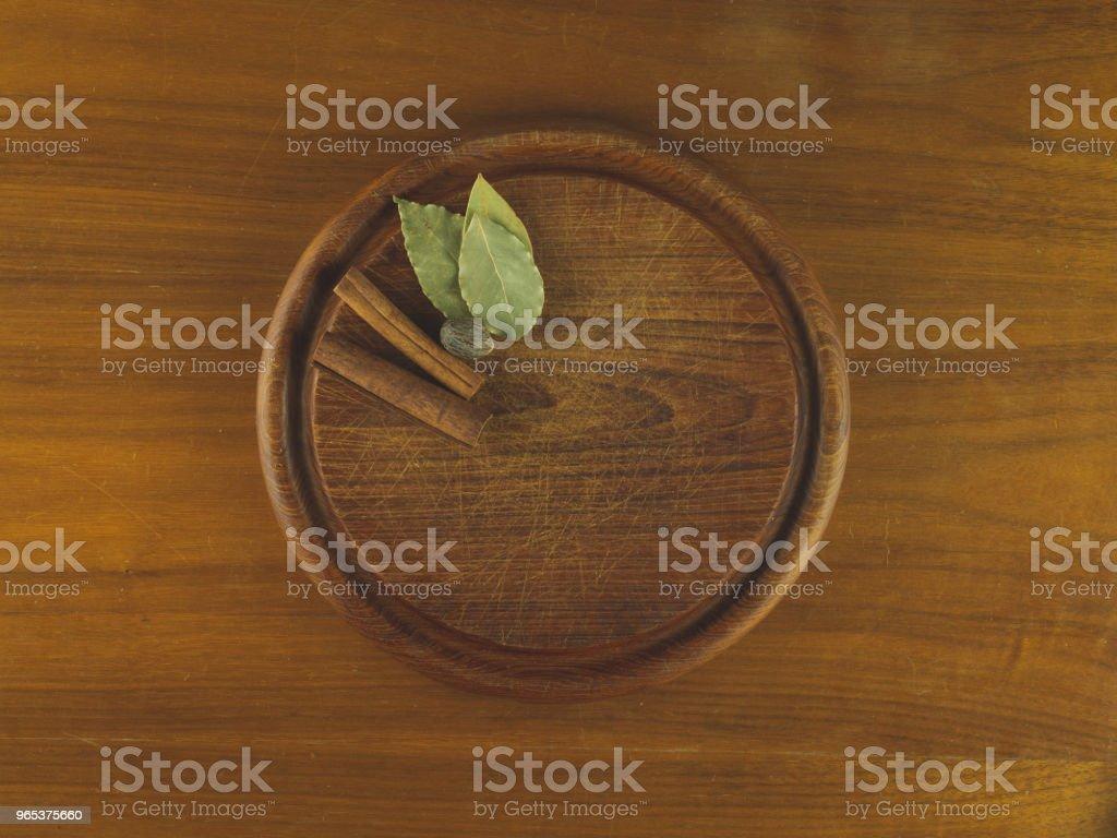 Round wooden cutting board with nutmeg, cinnamon, and bay leaves zbiór zdjęć royalty-free
