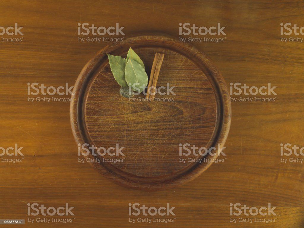 Round wooden cutting board with nutmeg, cinnamon, and bay leaves zbiór zdjęć royalty-free