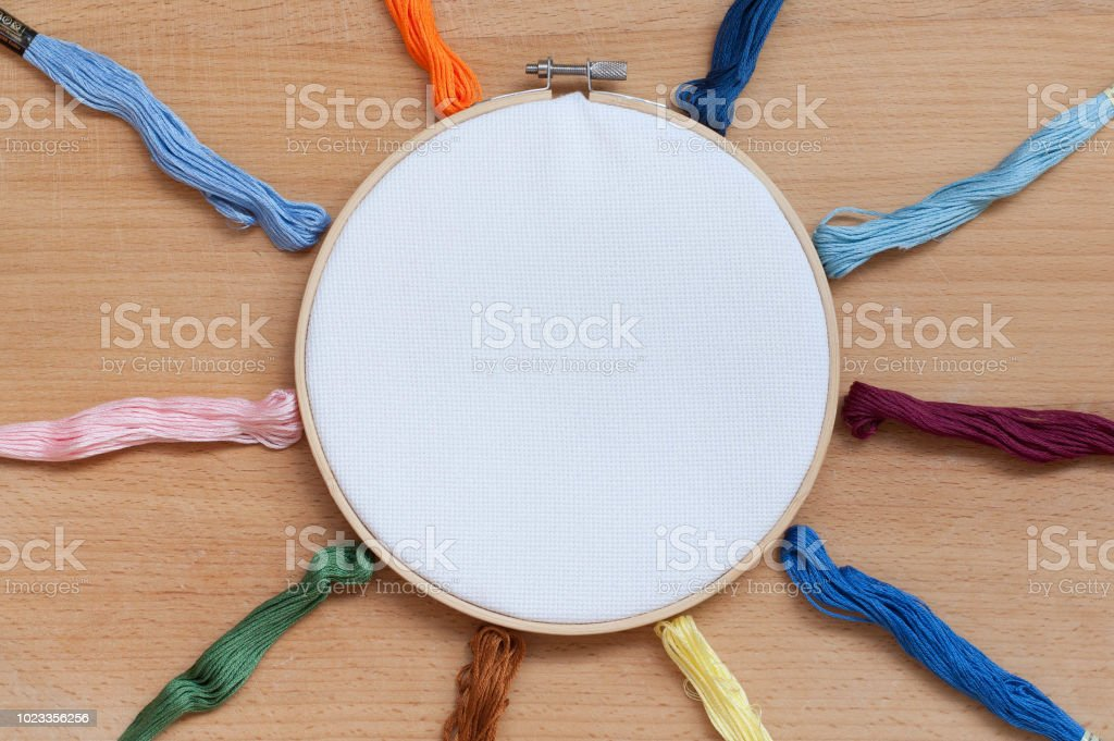 Round wooden hoop with a white cloth on a wooden background.