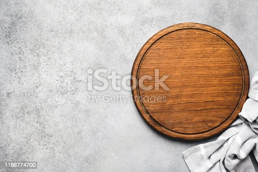 Round wooden pizza board on grey concrete background and grey linen textile. Copy space for text. Food background