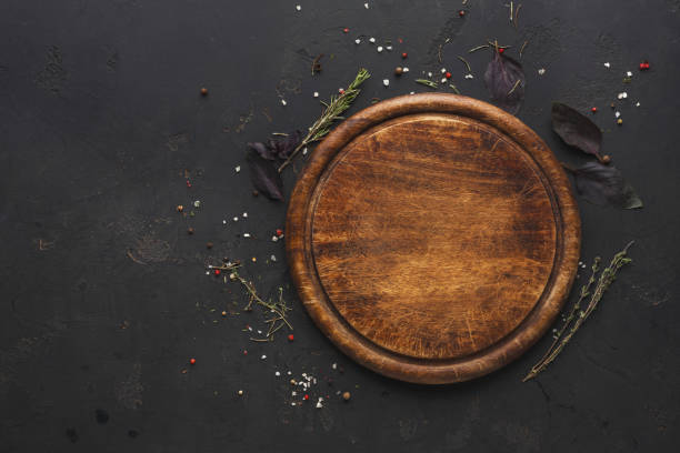 round wooden plate on dark wooden background top view - разделочная доска стоковые фото и изображения