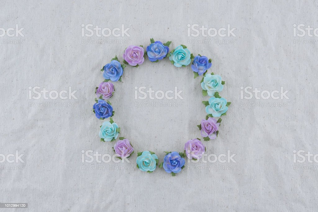 Round wreath made from blue tone rose paper flowers on muslin fabric...