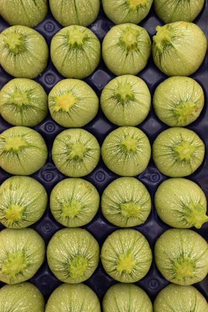 Round yellow zucchini on a market stall stock photo