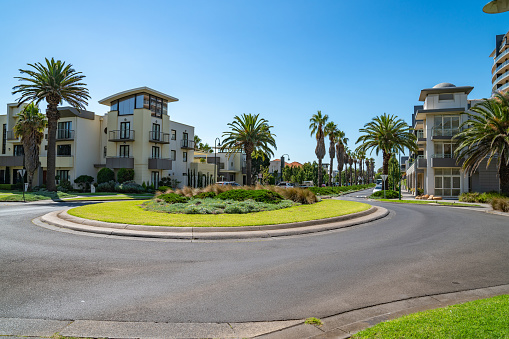 Roundabout and palm tree lined residential roads in modern seaside suburb and homes in Melbourne Australia.