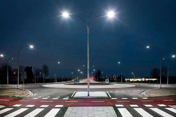au rond-point, illuminé par des spots à led au crépuscule - rond point carrefour photos et images de collection