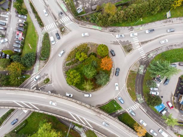 intersection de route de rond-point avec la circulation de véhicule et la vue aérienne verte d'arbres du drone affichant la forme et les voies circulaires, architecture de jonction de transport - rond point carrefour photos et images de collection