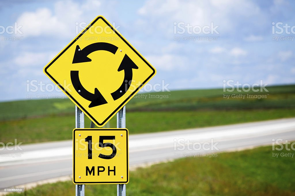 A roundabout traffic warning and speed sign in a rural area.