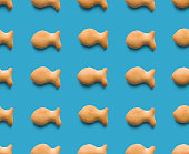 istock Rounded fresh crispy fish shaped cookies on light blue background. Seamless texture. Top view 1187185012