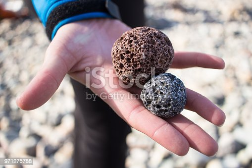 A hand holding two lava rocks that have been rounded by the action of the ocean