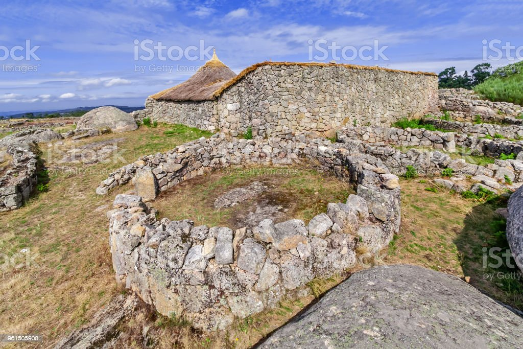 Roundhouse ruins and the reconstructed family nucleus building in Citania de Sanfins. stock photo