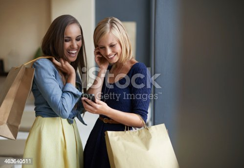 Two friends out shopping and reading a text message