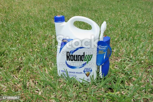 West Palm Beach, USA - April 29, 2013: A container of Roundup Weed and Grass Killer on a grass lawn. Roundup is a popular gardening and landscaping product that is manufactured by the Scotts Company LLC.