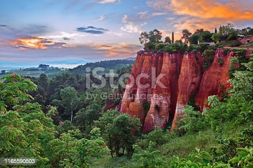Roussillon, Provence, France: landscape at dawn of the red ochre rocks and the green valley in the nature park of Luberon