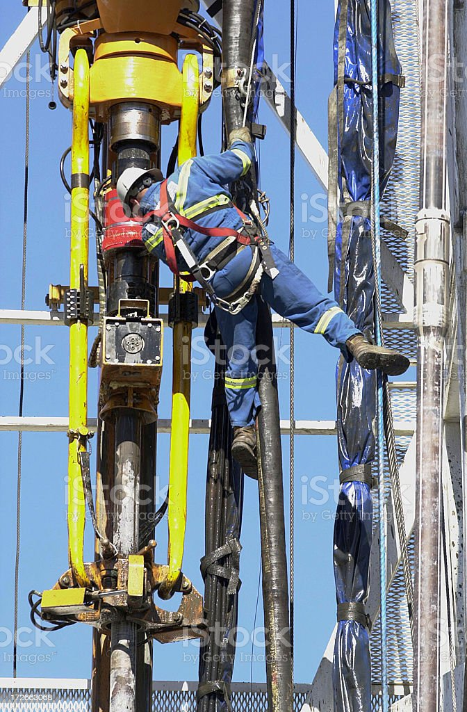 Roustabout checks drilling head on tower royalty-free stock photo