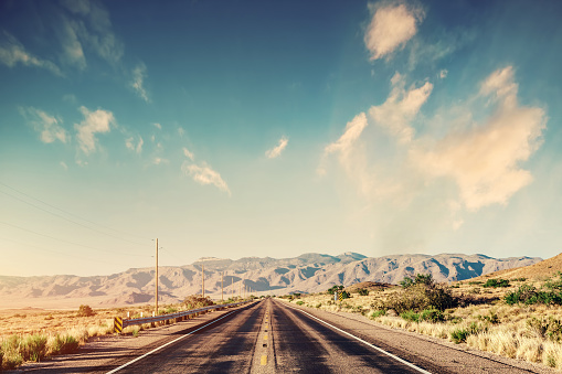 Route 66 classic old road in desert and mountain scenery in the USA. Vintage tone